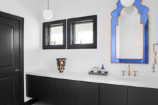 05 Black and white bathroom is spruced up with a whimsy blue frame mirror and an orange patterned rug