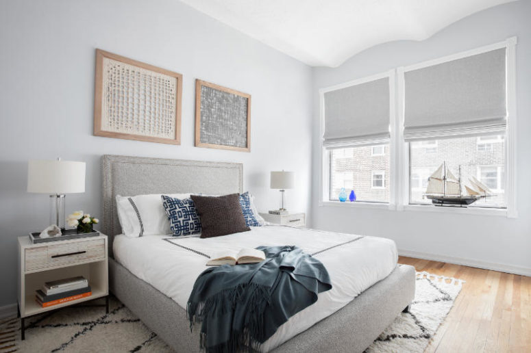 The bedroom is no less calm than the living room, there's an upholstered bed, a textural wall art and some cozy fabrics