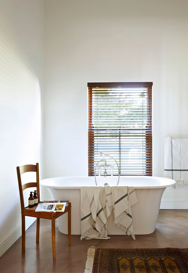 The master bathroom is an effortlessly chic place with a free standing bathtub next to the window covered with shutters