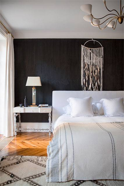 The master bedroom has a chalkboard headboard wall, a Moroccan rug and a dreamcatcher