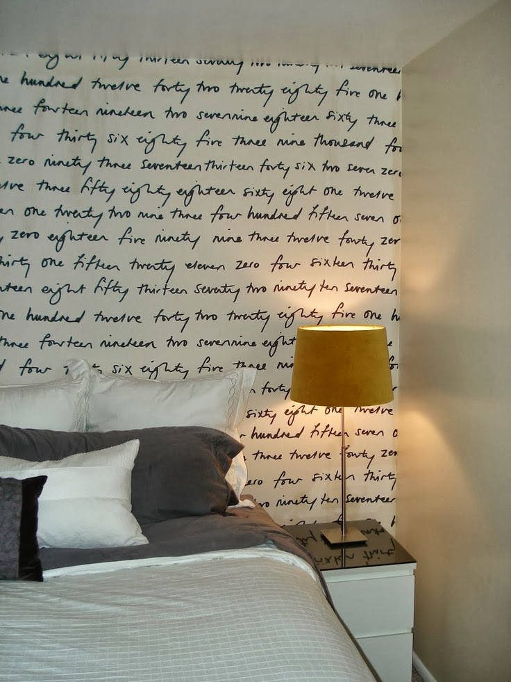 fabric handwriting accent wall doubles as a headboard in this bedroom