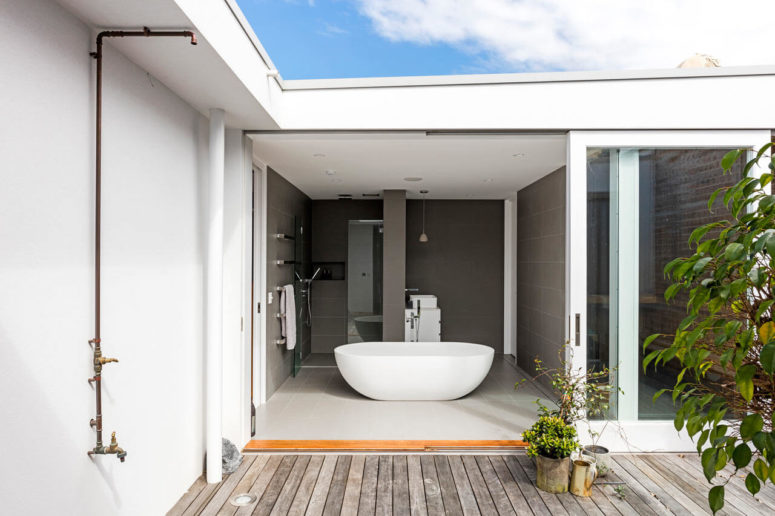 The bathroom is done in grey, with a minimalist feel, and it may be opened outside with a glass door