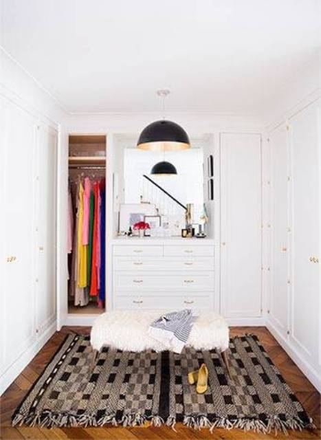 The small closet has white cabinets, a Moroccan rug and a faux fur ottoman