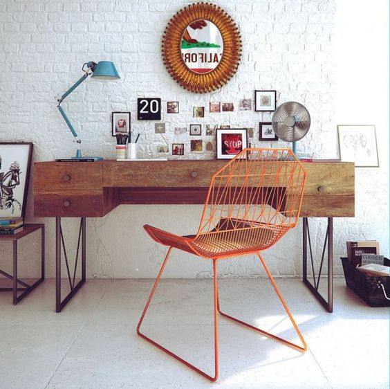 mid-century modern home office with a boho flavor is complemented with a white brick wall