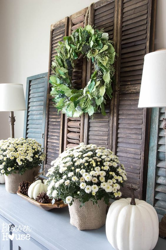 neutral fall mantel with faux pumpkins and potted flowers