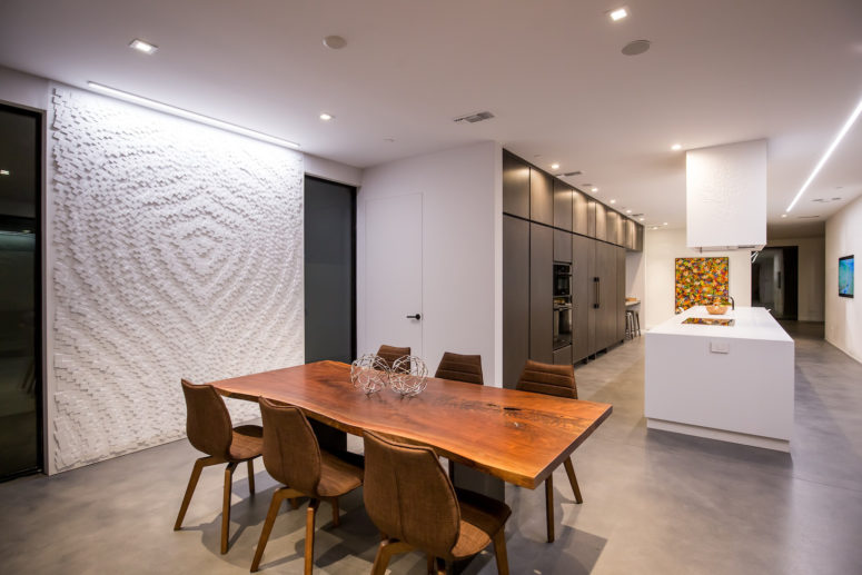 The dining space is accentuated with a large textural geometric wall art