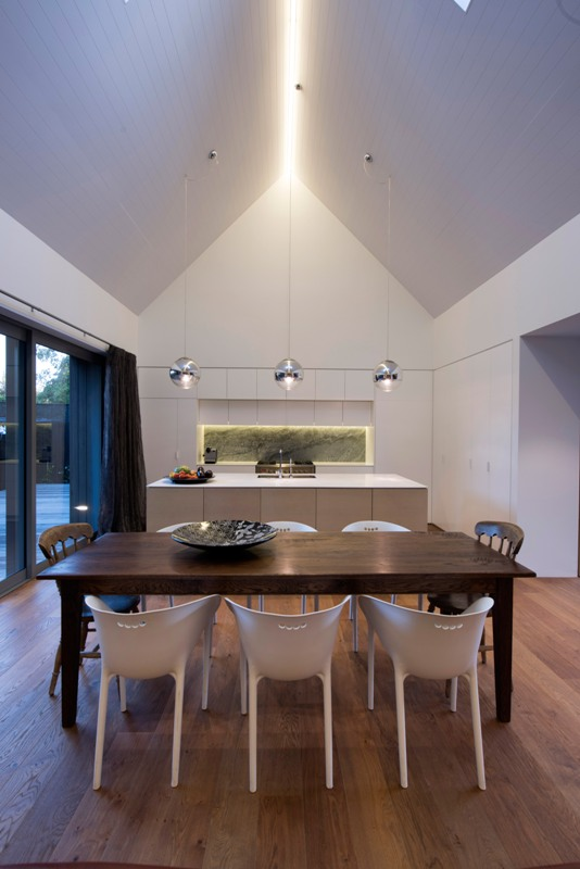 The kitchen is modern and minimalist, with a large glass door