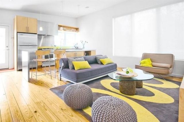 airy living room with grey and yellow details looks very cheerful, and yellowish wooden floors add a sunny touch
