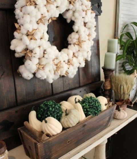 boxwood planter with white pumpkins and silk flowers, a cotton wreath