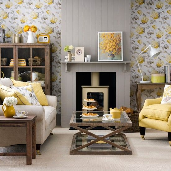 grey and yellow floral wallpaper, a grey fireplace panel and a yellow chair  and pillows