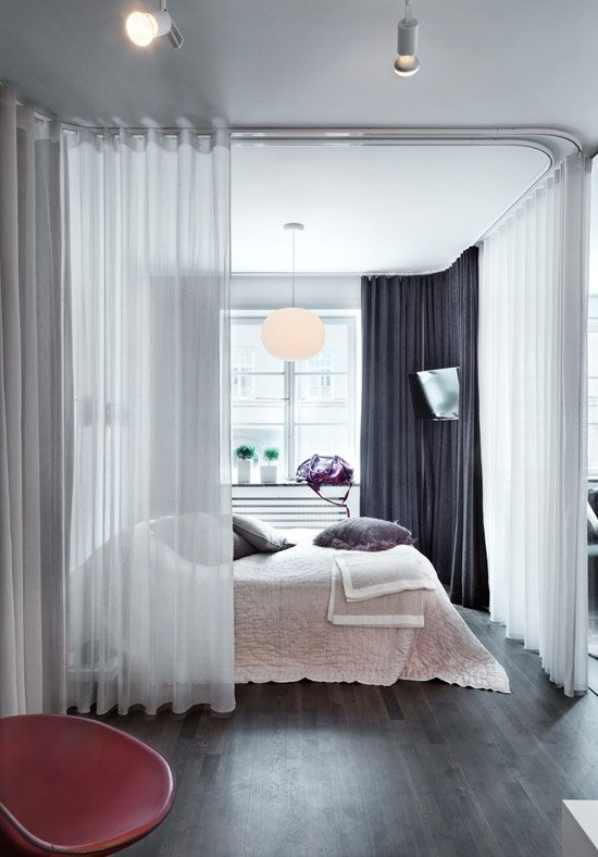 picture of sheer white curtains divide the bedroom area