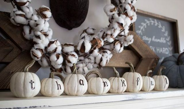 simple mantel decor with white faux pumpkins and a cotton wreath