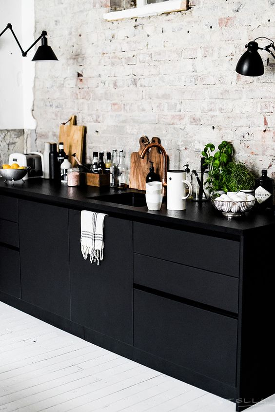 sleek black cabinets and vintage whitewashed wall leave an impression