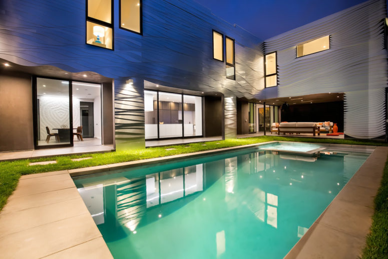 Almost every space is opened to the large pool, and the outer clad of the house reminds of the ocean waves