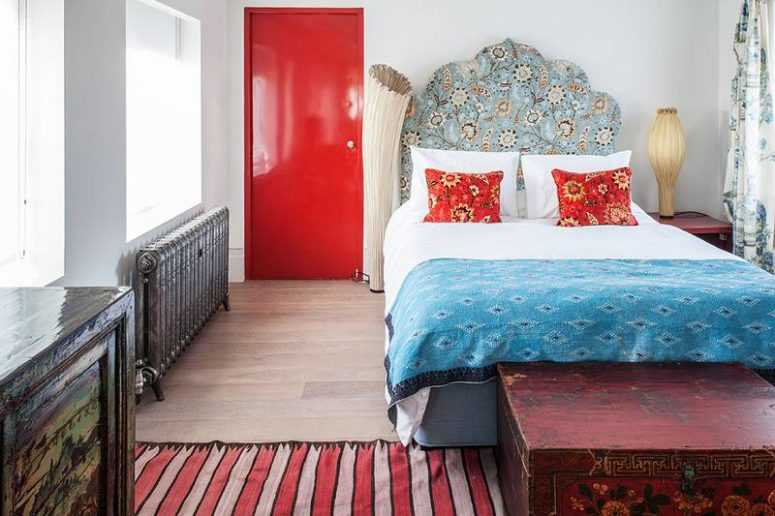 The master bedroom looks like a bold artwork, there's a bold red door, a vintage radiator, oriental textiles and a headboard