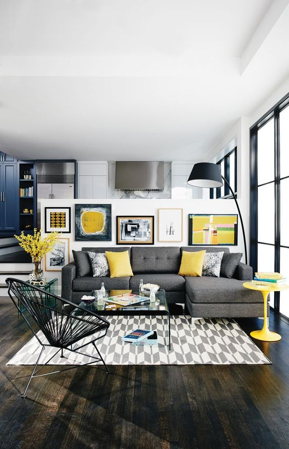 Modern Living Room With A Grey Sofa, Yellow Pillows, A Table, An Artwork