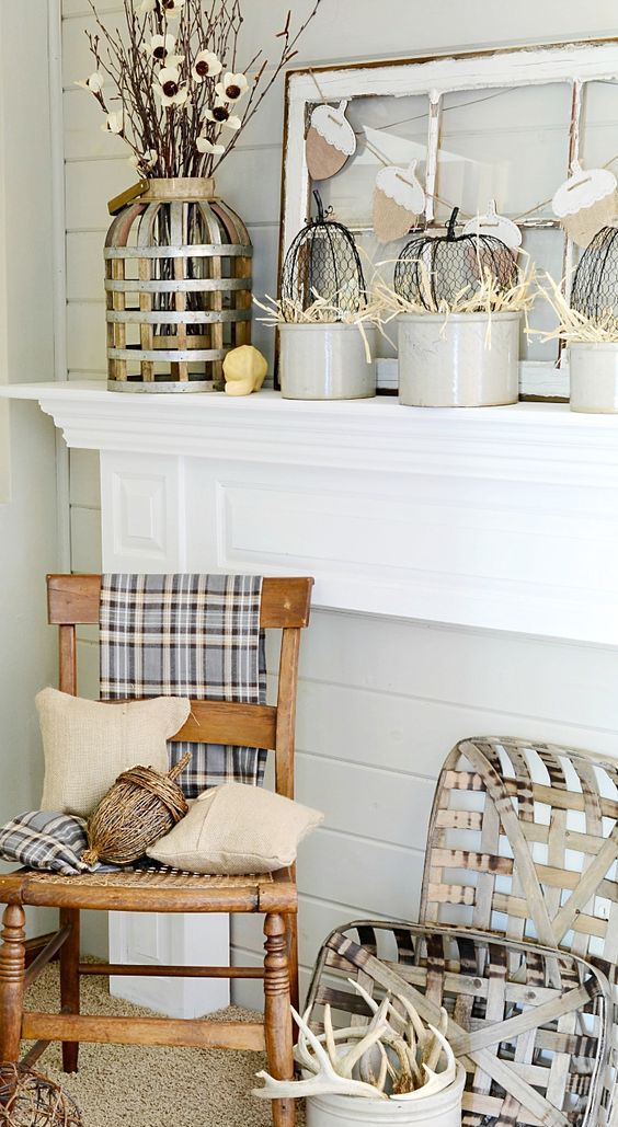 neutral fall mantel incorporating farmhouse style with vintage wooden chair, tobacco baskets, and burlap pillows