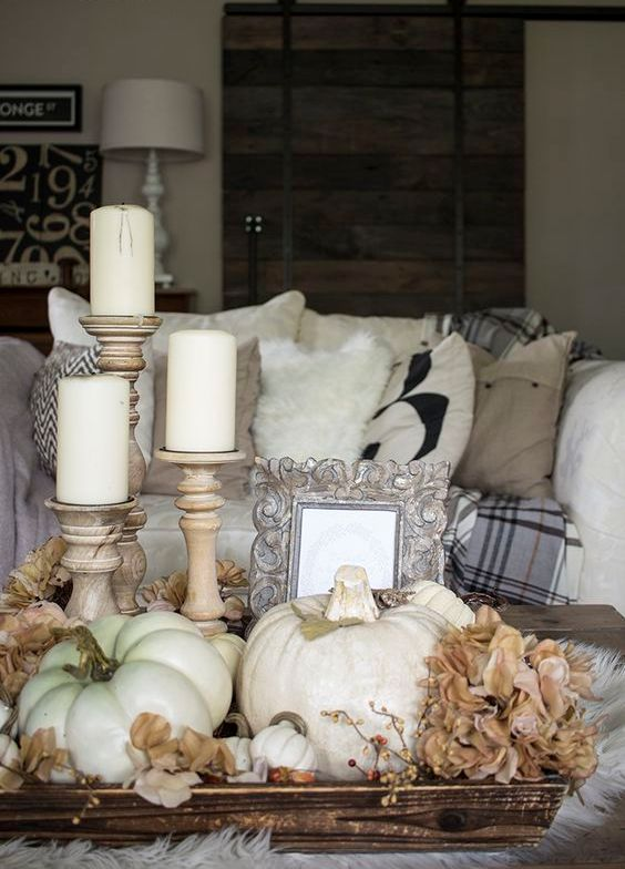 coffee table display with silk flowers, pillar candles and white pumpkins