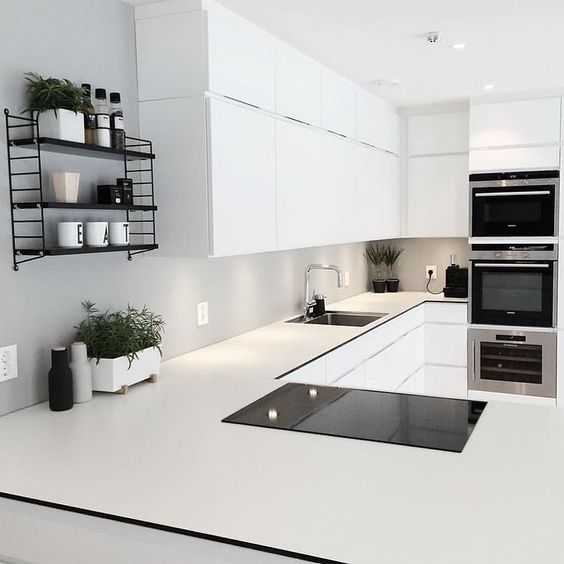 black pocket string shelf in an all white kitchen and the living green elements keep the space looking fresh and alive