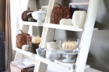 11 ladder-style shelf with white pumpkins, lanterns and wire pumpkins with lights