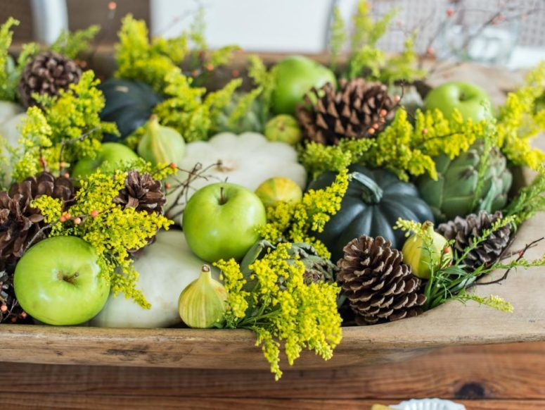 seasonal pumpkins, gourds, pinecones and flowering branches in a wooden bowl