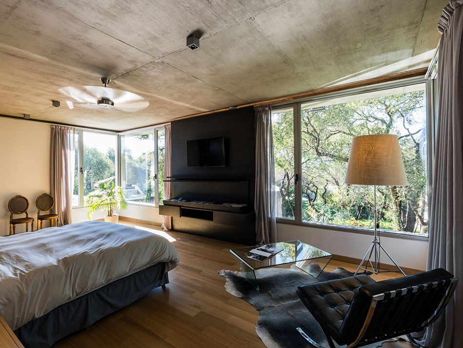 the bedroom is also highlighted with black and there are large windows to capture the views
