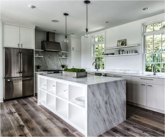 waterfall countertop hides a shelving unit inside the kitchen island