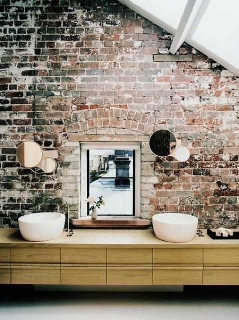 exposed brick wall with mirrors on it