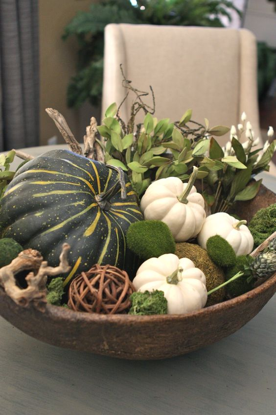 wooden bowl filled with leaves, gourds, pumpkins and moss
