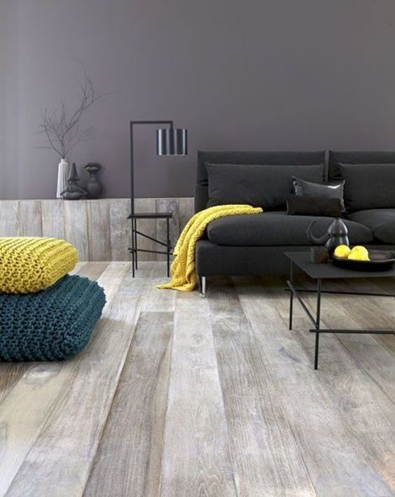 a minimal living room in grey and black can be spruced up with a yellow throw and a pillow