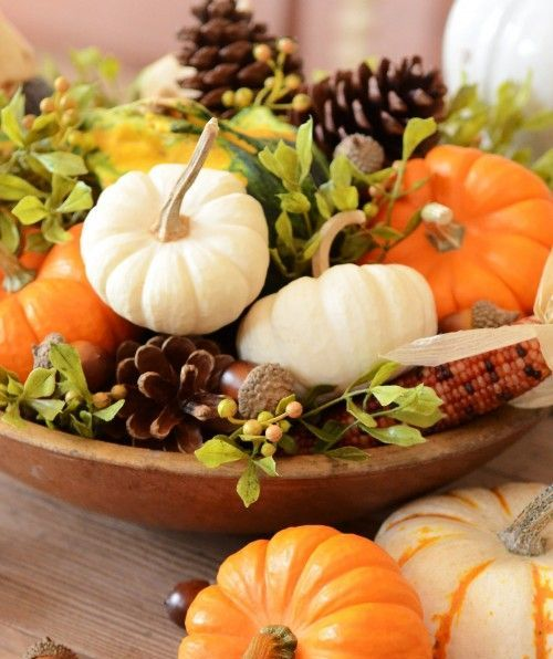 wooden bowl filled with pumpkins, corn, pinecones and greenery