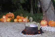 14 yard haunt with a skeleton in a cauldron and jack-o-lanterns