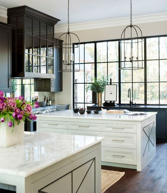 Airy Kitchen With Two White Kitchen Islands And A Large Black Framed Window