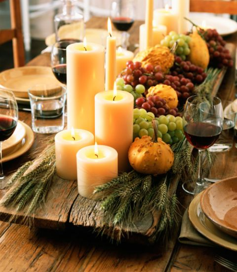 wooden board with grapes, gourds and candles