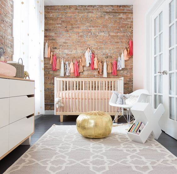 a little one's nursery is given extra character when focused on the exposed brick wall