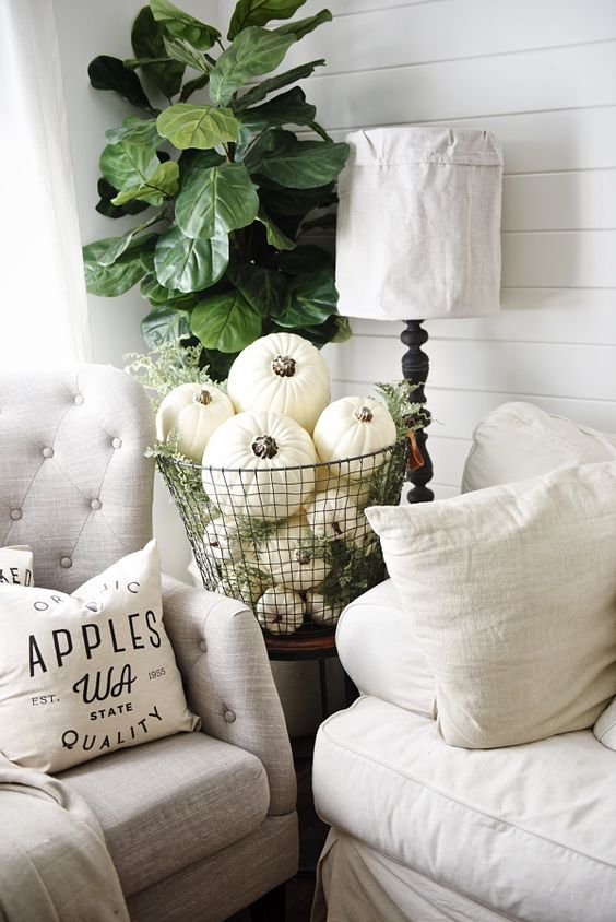 neutral fall decor with a wire basket full of pumpkins