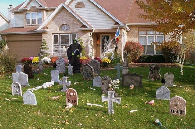 graveyard decor with a witch figure standing next to it will turn your entrance into a spooky one