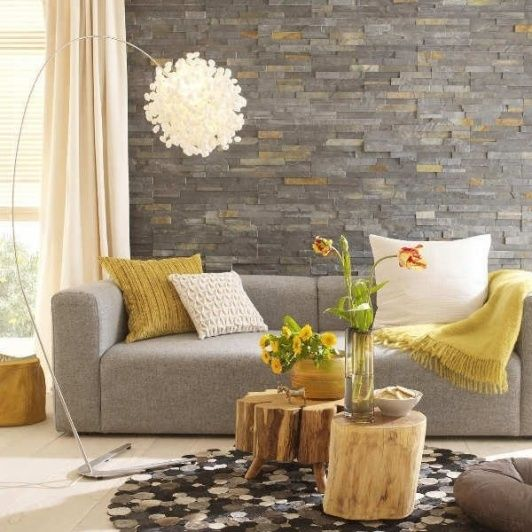 grey stone accent wall, a dove grey sofa and yellow textiles