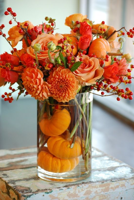 orange dahlias, roses, berries and pumpkins inside the glass vase