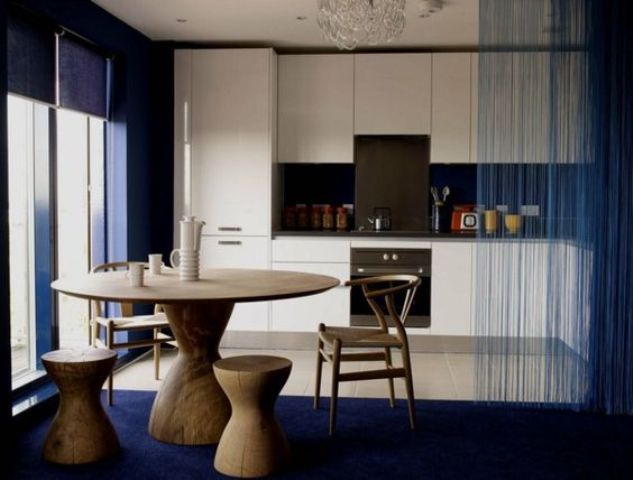 sheer blue curtain continues the decor and divides the dining zone from the kitchen