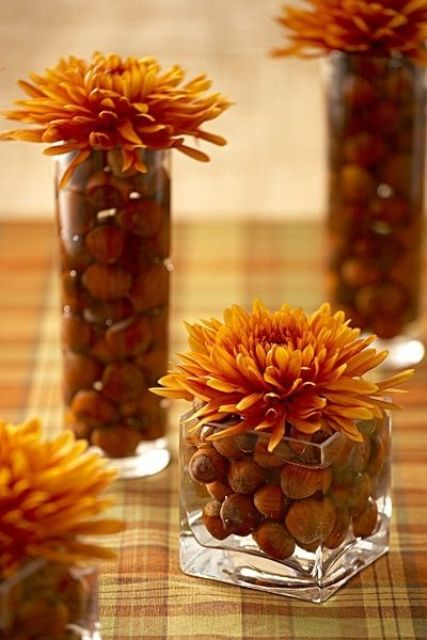 vases and jars filled with hazelnuts and bold orange flowers