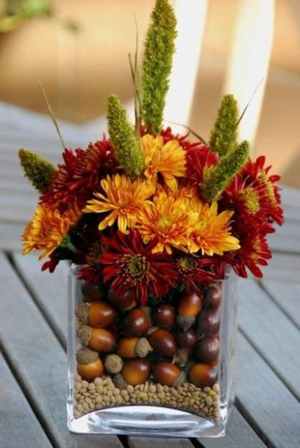 acorns put into a glass vase and a bold floral arrangement over them