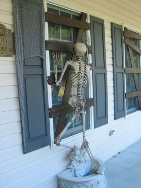 cardboard affixed to window to make it look boarded up and skeleton proped to look like it's trying to get in