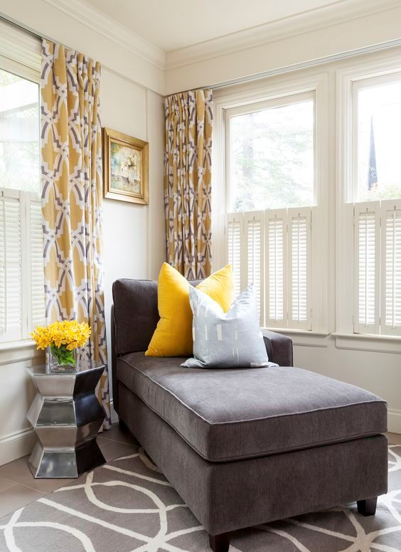 a charcoal couch and a bold yellow pillow look very contrasting