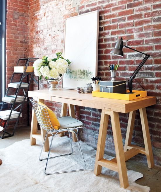 chic modern home office with a red brick wall and a wooden desk