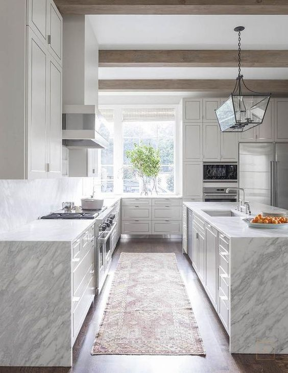 grey and white quartzite waterfall edge countertops emphasize modern aesthetics