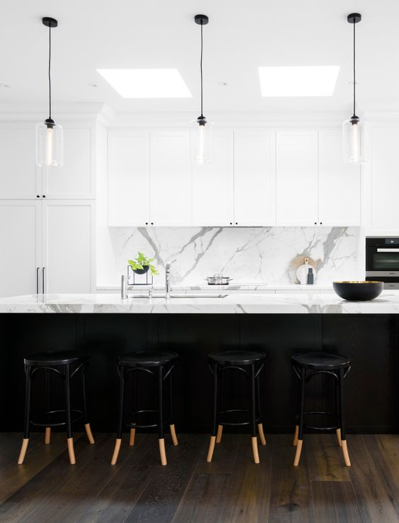white marble benchtops and splashback, white shaker cabinets with minimal black handles, glass pendant lights with black cords