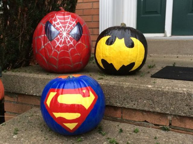 painted Batman, Superman and Spiderman pumpkins for outdoor decor