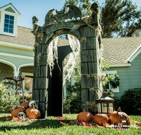 crypt gateway decorated with pumpkins, skulls, lanterns and spiderweb