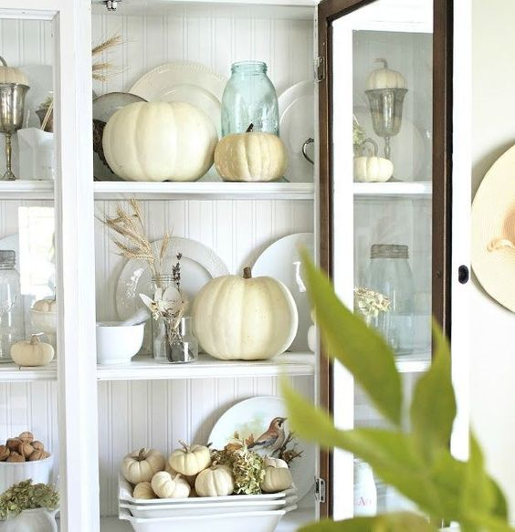 place neutral pumpkins and wheat into your glass kitchen cabinet